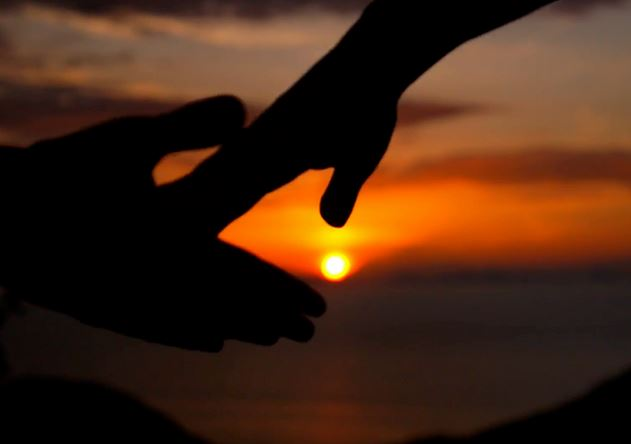 hands touching sunset